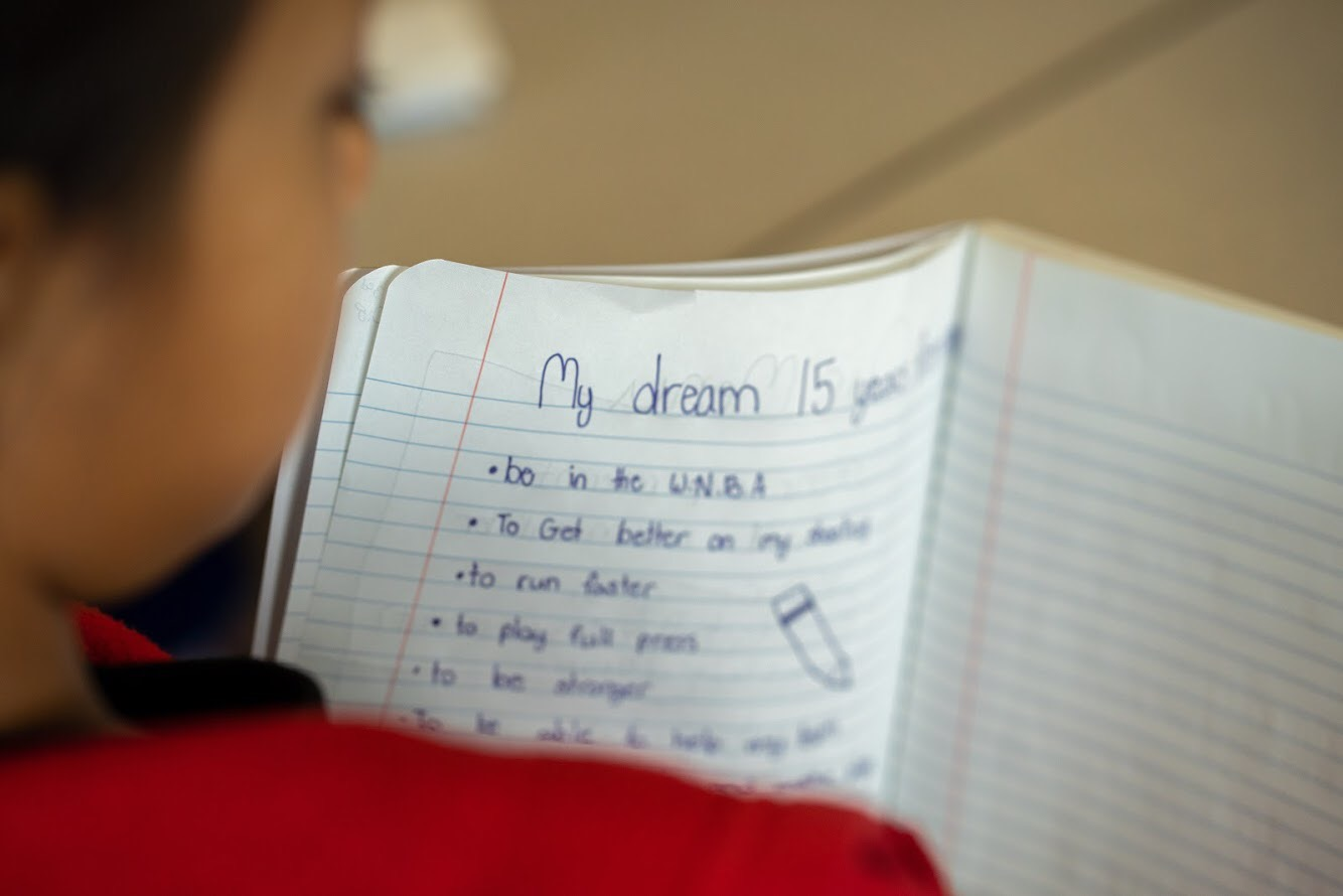 over a child's shoulder, a written list of goals and dreams