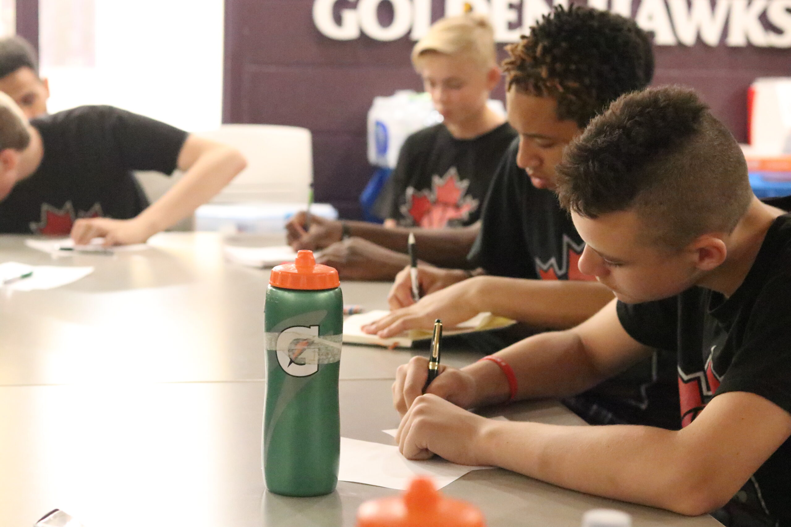a group of boys writing notes at an NBYMP workshop